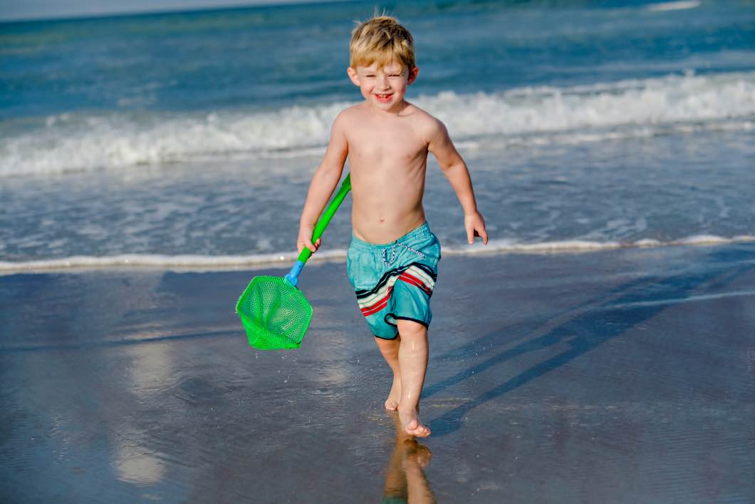child having fun daytona beach - Daytona Beach Family Vacation by Atlanta mom blogger Happily Hughes